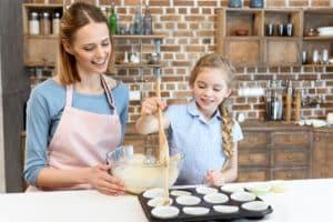 Mutter und Tochter backen Muffins